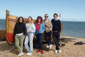 The Keepers Cottages team standing in front of a boat in Deal